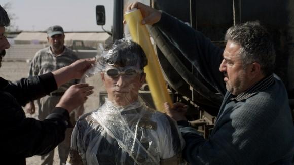 Siyar (Taher Abdullah Taher) wird mit Folie vor Öl geschützt; Standbild aus dem Film